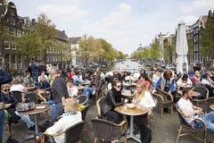 Many people enjoy nice spring day outside near canal in Amsterdam. Many people enjoy nice spring day outside on bridge over Singel canal in Amsterdam royalty free stock photo