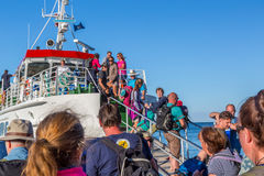 Many people entering a ship. Gotska sandon, Sweden - August 2, 2017: Ground view of crowd of people using a gangway to board a ship to leave the national park Stock Photography