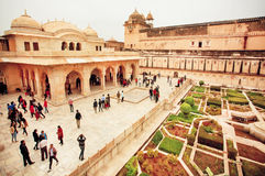 Many people in garden of the Amber Fort with historical stone palaces Royalty Free Stock Photo