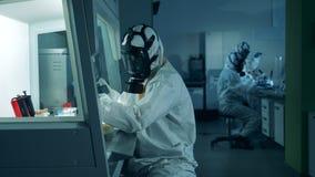 Many people in hazmat work in laboratory, researching coronavirus samples.