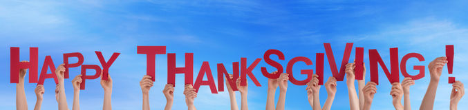 Many People Holding Happy Thanksgiving in the Sky Royalty Free Stock Images