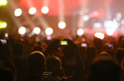 Man using smart phone at live concert and many people. Many people and man taking smart phone at live concert and lights on stage royalty free stock photography