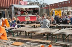 Many people meeting around tables and eating fast food at street market Reffen, urban area for start-ups. COPENHAGEN, DENMARK - SEPT 7: Many people meeting stock images