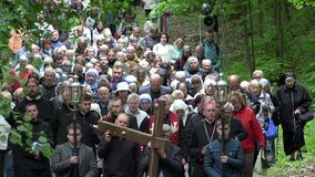 Many people participate in religion procession carry cross through forest path