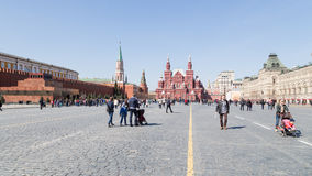 Many people on Red Square. Moscow - April 12, 2015: Citizens and tourists walking along the pavement on Moscow's Red Square and Lenin's mausoleum can be seen in Stock Photography