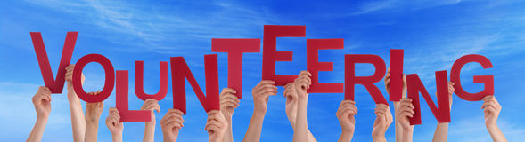 Many People Red Word Volunteering Blue Sky. Many Caucasian People And Hands Holding Red Letters Or Characters Building The English Word Volunteering On Blue Sky royalty free stock image