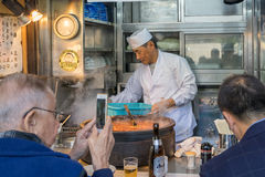 Many people shopping and eating some food at the Tsukiji market. TOKYO, JAPAN - NOV 18, 2016: Many people shopping and eating some food at the Tsukiji market royalty free stock images