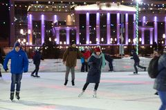 Many people skate in the evening on a city skating rink. royalty free stock photography