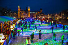 Many people skate on winter ice skating rink at night in front of the Rijksmuseum, a popular touristic destination in Amsterdam Royalty Free Stock Images