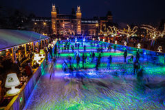 Many people skate on winter ice skating rink at night in front of the Rijksmuseum, a popular touristic destination in Amsterdam Stock Photos