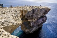 People standing in Azure Window in Malta. Many people standing on Azure Window in Malta Stock Photo