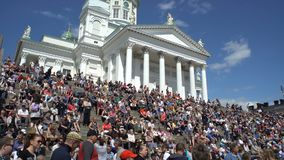 Many people, students and tourists sit on the steps in front of the Cathedral on the Senate Square in Helsinki. HELSINKI, FINLAND - JUNE 10, 2017: Many people stock footage