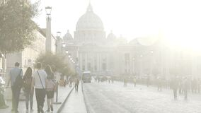 Many people walking brightly sunlit street, church in Vatican City, slow motion. Stock footage stock footage