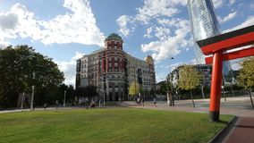 Many people walking in nice green city park, beautiful architecture, sunny day. Stock footage stock video footage