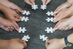 Many persons holding pieces of jigsaw puzzle,Teamwork concept,,Business connection,Success and strategy concept,Business accountin stock photography