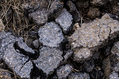 Many pieces of asphalt damage road as scrap, The asphalt scrap is mixed with some dry grass. Stock Photography