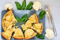 Many pieces of healthy cauliflower pie on the gray plate decorated with fresh basil leaves and vintage silver knife and fork royalty free stock photo