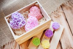 Beautiful fragrant bright multi-colored soaps in the form of hearts and flowers in a light wooden box on a wooden background royalty free stock image