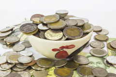 Many Pile of coins baht Thailand currency in yellow ceramic bowl. Stock Photo