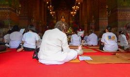 Many pilgrims praying at Buddhist temple in Bangkok, Thailand stock photo