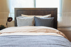 Many pillows on the bed and the bed head lamps. Stock Image