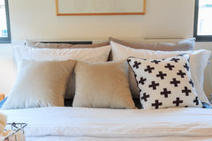 Many pillows on the bed have a picture frame. Stock Image