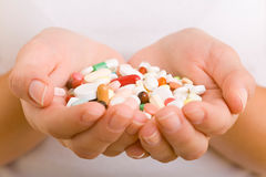 Many pills. Hands holding a variety of pills and capsules royalty free stock image