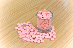 Many pink pills on wood table for health care concept Royalty Free Stock Images