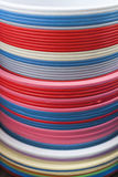 Plastic basins in many colors. Many plastic basins in different colors, as a stack on a open market, under sunlight Royalty Free Stock Image