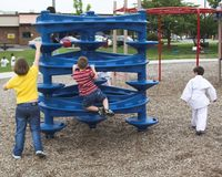 Many Playing. Three young children playing in park play area Stock Photos