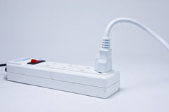 Many plugs plugged into electric power bar. Plug on a white background Royalty Free Stock Images