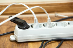 Many plugs plugged into electric power bar Stock Images