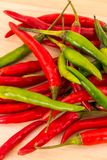 Many pods of long chili peppers green red contrasting fruits base bright contrasting on a wooden base royalty free stock photos