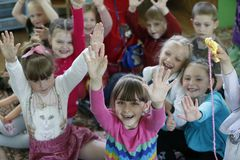 Many preschoolers. Belarus, the city of Gomel, May 16, 2016. Kindergarten Volotovskaya.Cheerful, joyful, a group of children raised their hands.Children are Stock Image