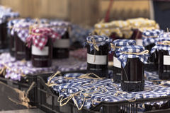 Many preserving jars with dark jam in a market Stock Photo
