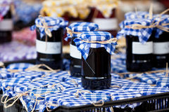 Many preserving jars with dark jam in a market Royalty Free Stock Images