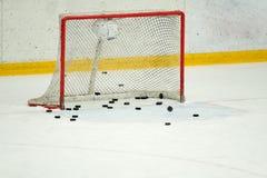 Many pucks in the hockey gates. Nobody Royalty Free Stock Photography