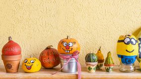Many pumpkins big and small with and without face. Before a yellow wall royalty free stock photos
