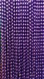 Many purple beads party neacklaces for celebrations or background. Macro close up vertical royalty free stock image