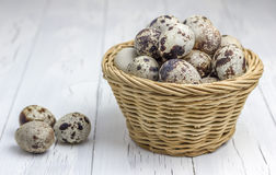 Many quail eggs in the basket. On the wooden table Stock Images