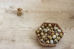 Many quail eggs. Lie in a beige basket that stands on a wooden table and in the distance one can see a toy rabbit Royalty Free Stock Image