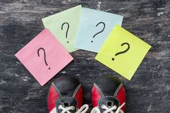 Many question marks before sneakers. Black background. royalty free stock photos
