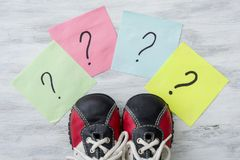 Many question marks before sneakers. Light background Royalty Free Stock Photo
