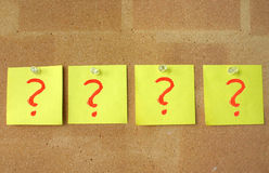 So many questions. Four yellow post-it notes with painted red question marks pinned to a corkboard, ideal metaphor of many questions asked Royalty Free Stock Photos