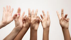 Many raised children`s expressive hands in a row. Expression of emotions between fingers royalty free stock photo