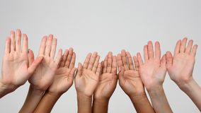 Many raised hands in a row. The many raised hands in a row Stock Photos