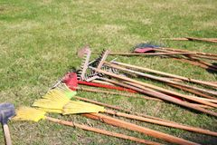 Many rakes, shovels, brooms and brushes for cleaning, arrangement of the territory, lie on the green royalty free stock images