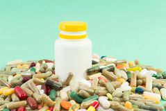 Many random pills with plastic recipient Royalty Free Stock Image