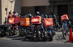 Many Rappi motorbikes parked outside a restaurant stock photo