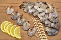 Many Raw  Shrimps On Skewer With Lemon On Wooden Background Royalty Free Stock Photos